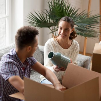 Smiling couple packing cardboard boxes together sitting on sofa in living room preparing to relocate, young happy woman holding vase helping man to unpack belongings moving in new home concept